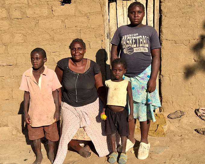 Estelle in front of her house with her children