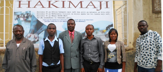 Mr Amosi Kalonge, Ward Executive Officer of Igamba Ward, Mbozi District, Mbeya Region, with Mbeya Highlands FM journalists Samuel Ndoni, Willick Simfukwe, Benny Mbilinyi, Safina Joel, Lusekelo Uswege. Photo: Amandine Oleffe