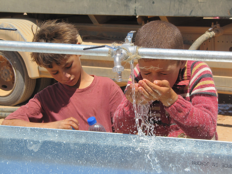 Syrian children enjoying clean water after the ICRC installed washing basins at several posts along the Syrian border in north-east Jordan. 05/07/2013 Photo credit: ICRC/ Alexandre Wagnieres