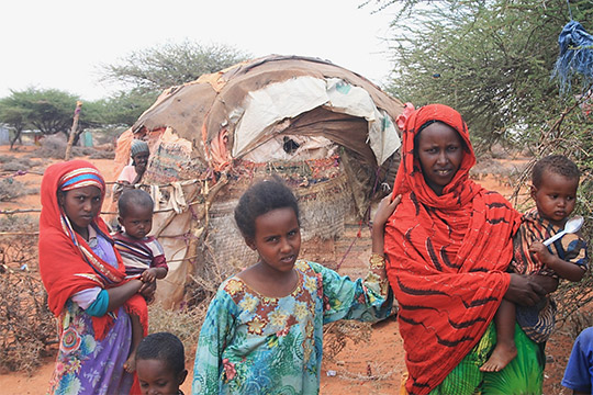 Nimco (right) outside her house with her children and some of her neighbours, all of whom live inside a minefield. Credit: Halo Trust
