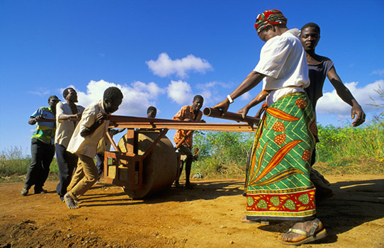Locals in Mozambique building a road with a hand operated roller. Photo by Panos