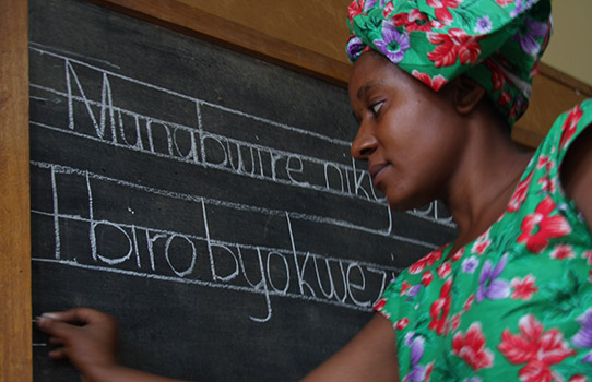 A teacher writing on a blackboard