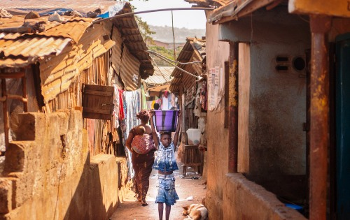 A girl walks down Kroobay Alley in Freetown, Sierra Leono. Photo: Irish Aid / Paul Sheehan